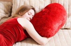 Junge Frau, die auf rotem Kissen schläft Stockbilder