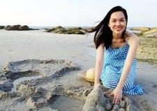 Junge Frau, die auf Sandstrand spielt Lizenzfreies Stockbild