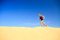 Junge Frau, die auf Sandwüstendünen läuft Lizenzfreie Stockfotografie