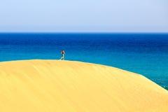Junge Frau, die auf Sandwüstendünen läuft Stockfotografie