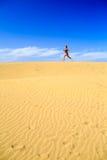 Junge Frau, die auf Sandwüstendünen läuft Lizenzfreie Stockfotos