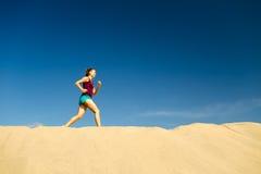 Junge Frau, die auf Sandwüstendünen läuft Stockbilder