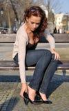 Junge Frau, die auf Schuhe sich setzt Stockbild