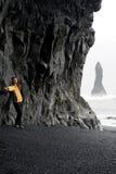 Junge Frau, die auf schwarzem Sandstrand nahe Vik aufwirft Lizenzfreies Stockfoto