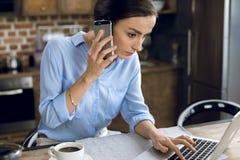 Junge Frau, die auf Smartphone bei der Anwendung des Laptops spricht Lizenzfreie Stockbilder