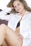 Junge Frau, die auf Sofa in der beiläufigen Abnutzung stillsteht Stockfoto