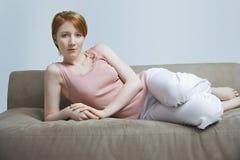 Junge Frau, die auf Sofa At Home liegt Lizenzfreie Stockfotos