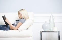Junge Frau, die auf Sofa-Lesebuch liegt Lizenzfreie Stockbilder