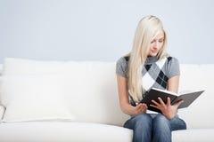 Junge Frau, die auf Sofa-Lesebuch sitzt Lizenzfreie Stockfotografie