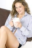 Junge Frau, die auf Sofa mit heißem Getränk sich entspannt Stockbilder