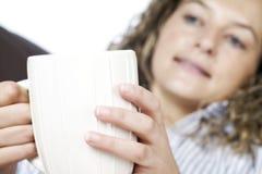 Junge Frau, die auf Sofa mit heißem Getränk sich entspannt Stockfotos