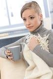 Junge Frau, die auf Sofa mit Tee stillsteht Lizenzfreies Stockfoto