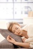 Junge Frau, die auf Sofa schläft lizenzfreie stockbilder