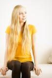 Junge Frau, die auf Sofa sitzt Lizenzfreie Stockbilder