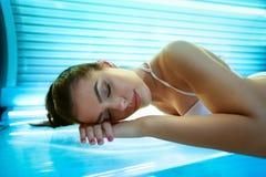 Junge Frau, die auf Solariumsbett legt Stockfoto