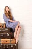 Junge Frau, die auf Stapel von Koffern aufwirft Stockfotos