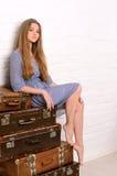 Junge Frau, die auf Stapel von Koffern aufwirft Stockbild
