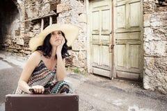Junge Frau, die auf Straße mit Koffer sitzt Stockfotos