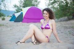Junge Frau, die auf Strand ein Sonnenbad nimmt Lizenzfreies Stockfoto