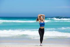 Junge Frau, die auf Strand mit den Armen angehoben geht Stockfoto
