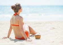 Junge Frau, die auf Strand mit Kokosnuss sitzt stockfotografie