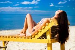 Junge Frau, die auf Strand sich entspannt Lizenzfreie Stockfotos
