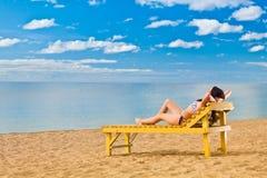 Junge Frau, die auf Strand sich entspannt Stockfotos