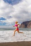Junge Frau, die auf Strand, Sommerinspiration läuft Stockfoto