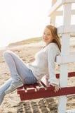 Junge Frau, die auf Strandleibwächterstuhl sitzt Lizenzfreies Stockfoto