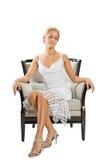 Junge Frau, die auf Stuhl sitzt Lizenzfreie Stockfotos