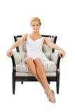 Junge Frau, die auf Stuhl sitzt Lizenzfreie Stockbilder