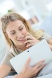 Junge Frau, die auf Tablette websurfing ist Lizenzfreies Stockfoto