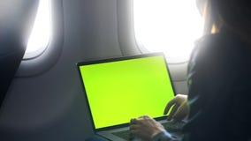 Junge Frau, die auf Tastatur schreibt und im Flugzeug sitzt stock video