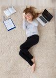 Junge Frau, die auf Teppich liegt Stockbild