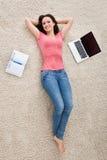 Junge Frau, die auf Teppich liegt Stockfoto