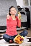 Junge Frau, die auf Teppich sitzt und Früchte genießt Stockbilder