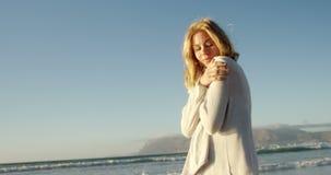 Junge Frau, die auf Ufer am Strand geht stock footage