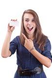 Junge Frau, die auf unbelegte Karte in ihrer Hand zeigt Stockfotografie