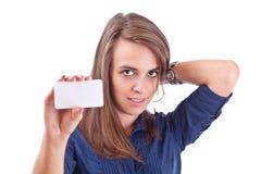 Junge Frau, die auf unbelegte Karte in ihrer Hand zeigt Stockfoto