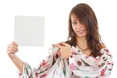 Junge Frau, die auf unbelegte Karte in ihrer Hand zeigt Stockbild