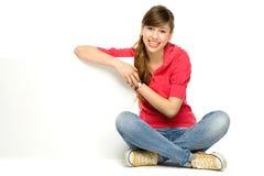 Junge Frau, die auf unbelegtem Plakat sich lehnt Stockfotografie