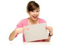 Junge Frau, die auf unbelegtes Plakat zeigt Lizenzfreie Stockbilder