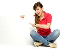 Junge Frau, die auf unbelegtes Plakat zeigt Lizenzfreie Stockfotos