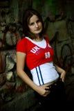 Junge Frau, die auf Wand sich lehnt Stockfotografie