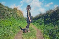 Junge Frau, die auf Weg in der Landschaft steht Lizenzfreie Stockbilder