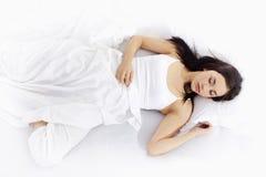 Junge Frau, die auf weißem Bett schläft Stockfoto