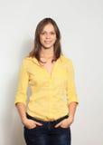 Junge Frau, die auf weißem Hintergrund lächelt Lizenzfreies Stockbild