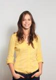 junge Frau, die auf weißem Hintergrund lächelt Lizenzfreie Stockfotografie