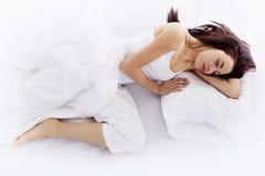 Junge Frau, die auf weißem Bett schläft Lizenzfreie Stockfotografie