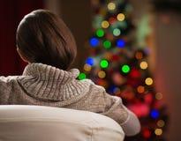 Junge Frau, die auf Weihnachtsbaum schaut. Hintere Ansicht Stockfoto